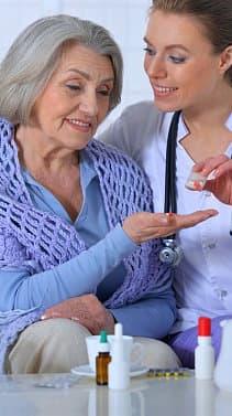 nurse giving medicine to her patient